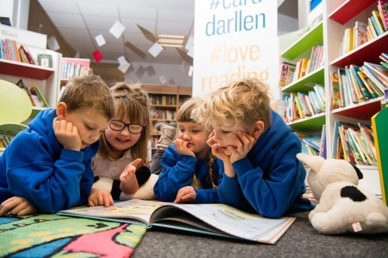 Primary schoolchildren lying on the floor of a library reading a book